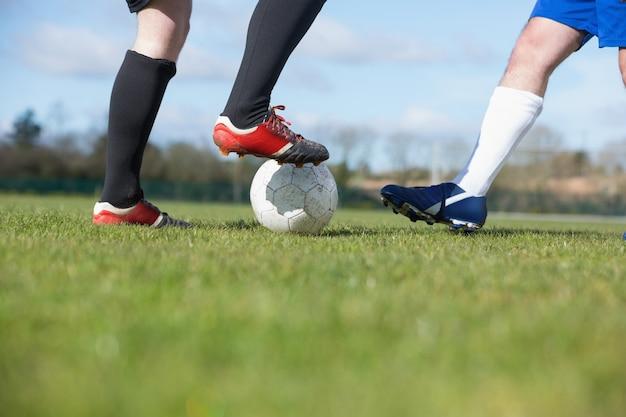 ピッチでボールに取り組むサッカー選手