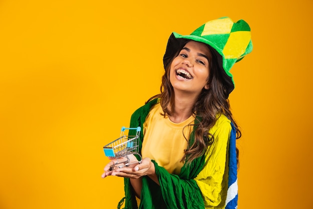 サッカーのプロモーション。ブラジルの服を着て手にミニショッピングカートを持っている女性。