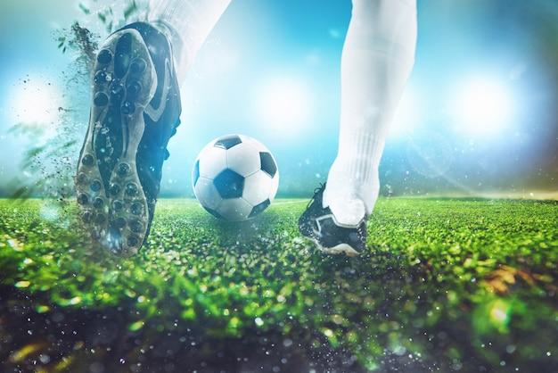 공을 치는 축구 신발의 가까이와 밤 경기에서 축구 장면