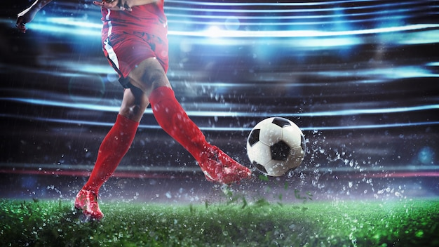 힘으로 공을 차는 빨간 제복을 입은 선수와 야간 경기에서 축구 장면