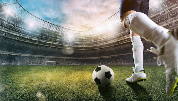 Football scene at the stadium with close up of a soccer shoe kicking the ball