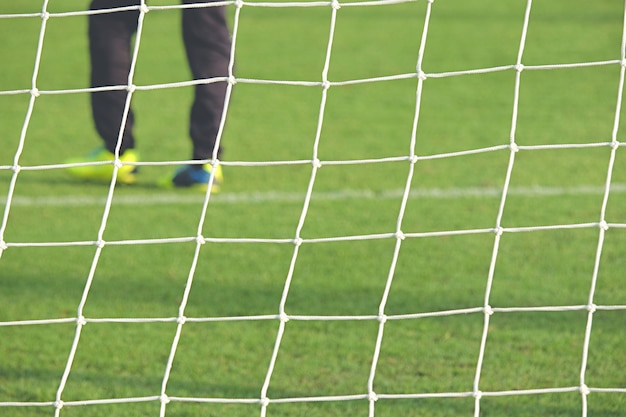 Football soccer goal net in focus with some players having training.