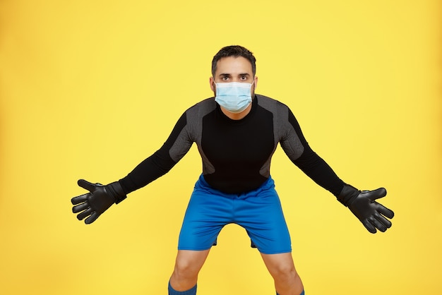 Football soccer goalkeeper trying to make a stop with a mask on his face due to the covid19 coronavirus pandemic on a yellow wall