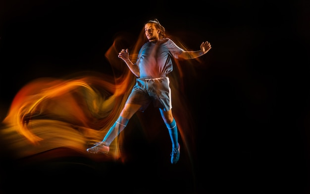 Football or soccer player on black background in mixed light fire shadows
