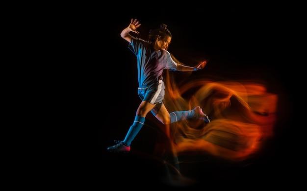 Giocatore di calcio o di calcio su sfondo nero in ombre di fuoco a luce mista