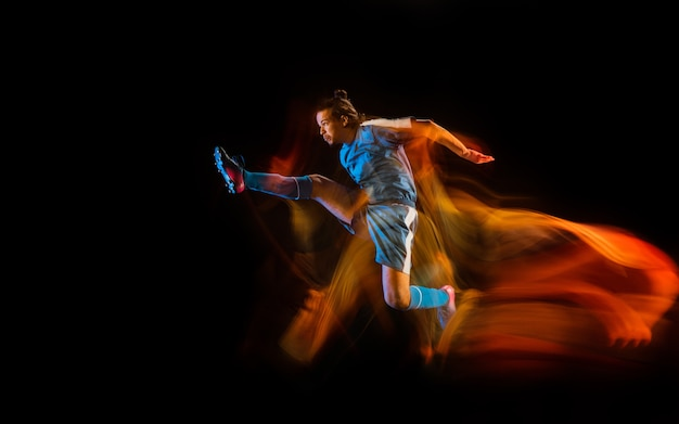 Football or soccer player on black studio