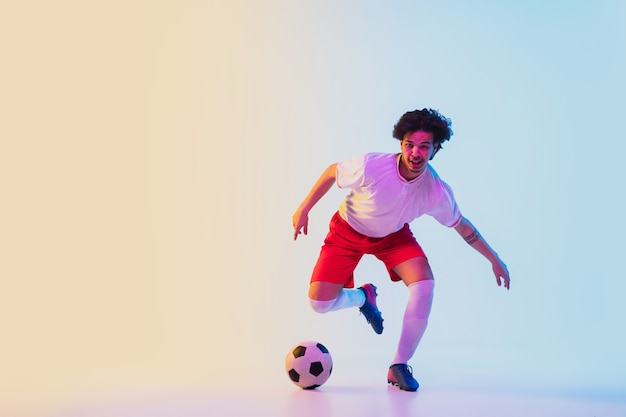 Football or soccer player on gradient in neon light