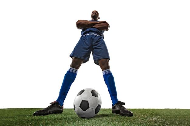 Giocatore di calcio o di calcio sul muro bianco con erba.