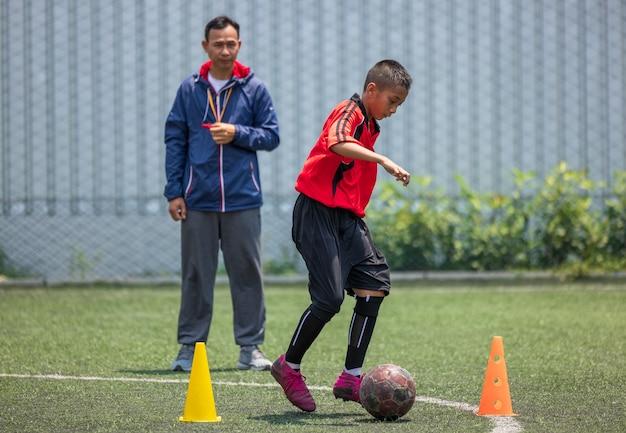 아이들을위한 축구 축구 훈련. 게임 계획을 설명하는 코치. 축구 기술을 향상시키는 어린 소년들 현지 태국