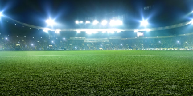 サッカースタジアム、光沢のあるライト、フィールドグラスからの眺め。芝生、遊び場に誰もいない、宇宙にゲームファンがいるトリビューン