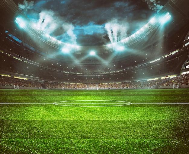 야간 경기를 기다리는 팬들로 가득한 스탠드가있는 축구 경기장