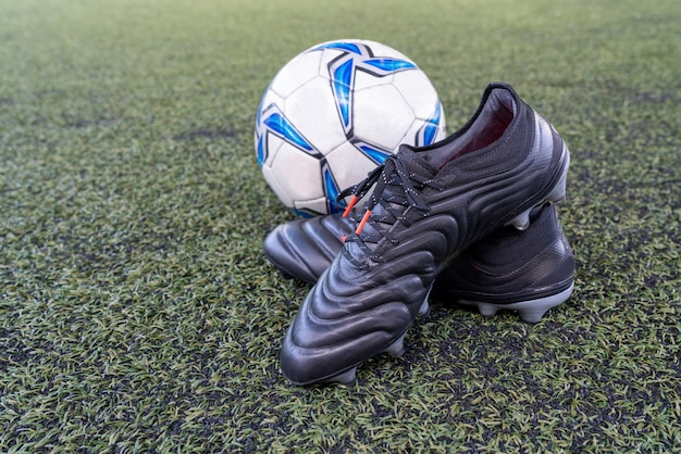 Football stud shoes with soccer ball on artificial grass field