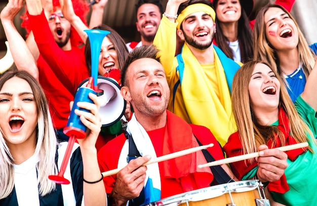 Football supporter fans cheering with drums watching soccer cup match at stadium bleachers