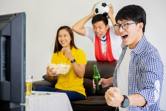 Football supporters having fun and celebrate during watching football game on tv at home