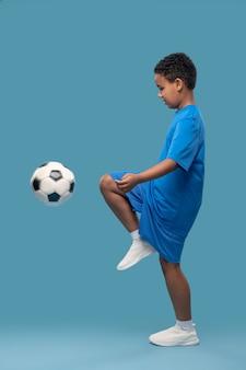 축구 훈련. 집중된 초등학교 나이 소년 아프리카 계 미국인 연습 축구 훈련의 프로필