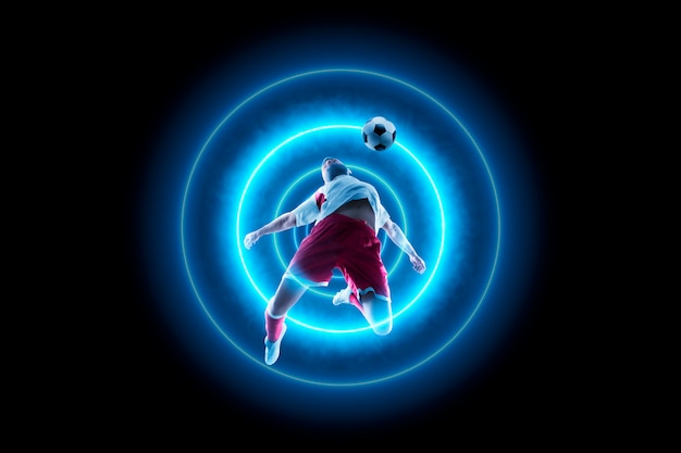 Footballer is dribbling with the ball. blue neon light