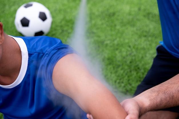 파란 셔츠를 입고 축구 선수는 레이스 도중 잔디밭에서 다친 검은 바지.