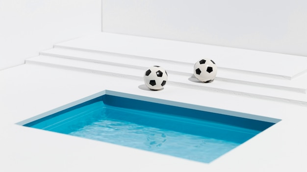 Footballs next to small swimming pool