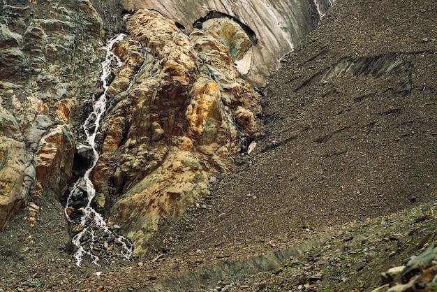 巨大な氷河の丘陵地帯。雪と氷のある驚くべき岩のレリーフ。小さな滝のある素晴らしい巨大な山の岩の自然の壁。