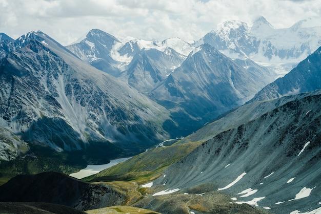 Тропинка через холмы к красивой горной долине с озером. огромные ледниковые горы под серым облачным небом. потрясающий драматический альпийский пейзаж со снежными горами и ледниками. атмосферные пейзажи.