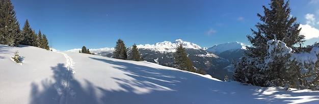 푸른 하늘 아래 눈 덮인 산을 건너는 신선한 눈에 발자국