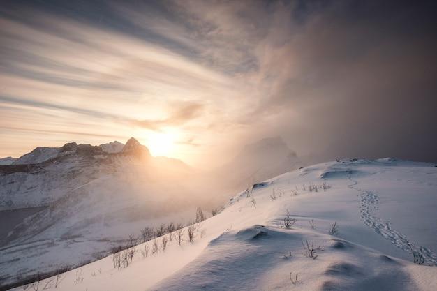 산맥에서 일출과 눈 언덕에 발자국