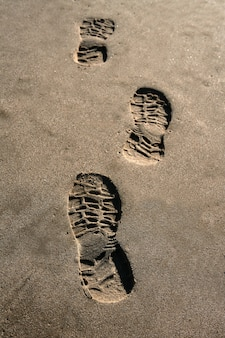 Footprint shoe on beach brown sand background