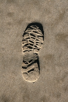 茶色の砂浜のテクスチャ印刷にフットプリントの靴