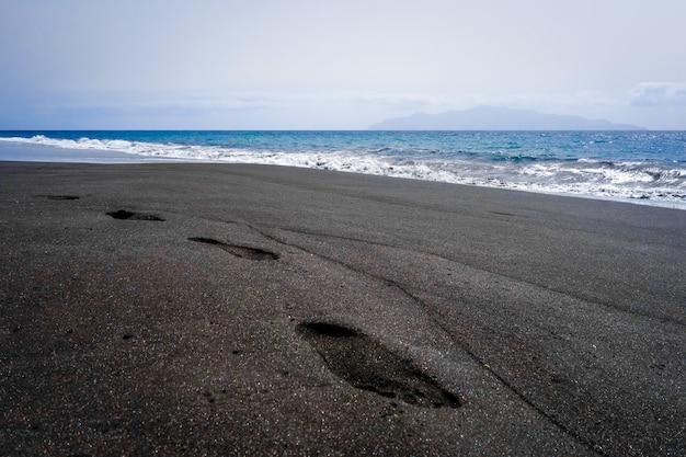 Footprints in black sand beach, fogo island, cape verde, africa