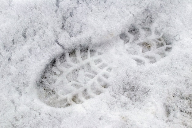 Footprints from shoes on wet snow, winter background
