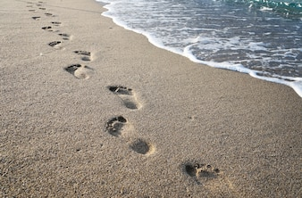 Footprints in the sand near the sea waves