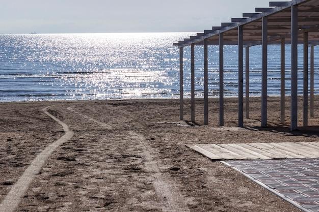 Следы людей на песке. морской пляж на закате. пятна солнца на воде. навес от солнца на пляже. среда. естественный фон