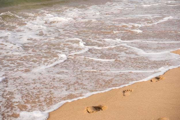 Следы на песчаном пляже. концепция путешествия