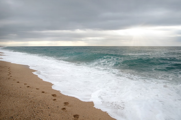 Следы на песке на пустом пляже. естественный фон