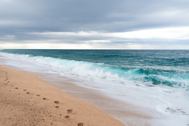 Следы на песке на пустом пляже