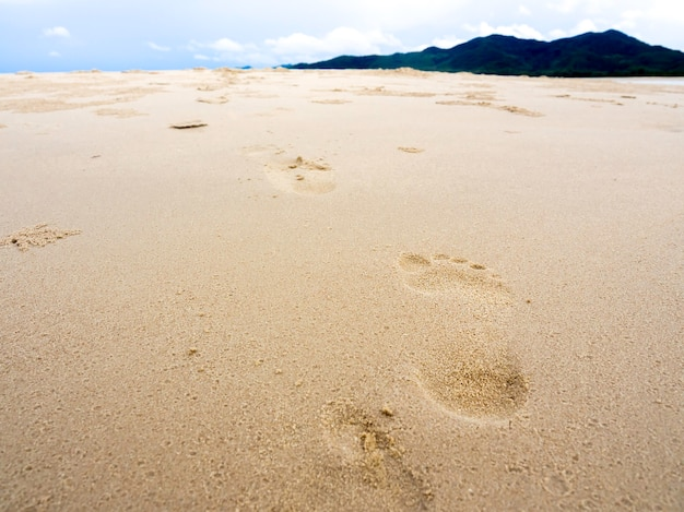 Footprints on the sant with blue sky and mountains in the background