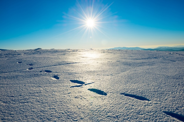 Footprints on the snow. bright landscape with sun in winter mountains.