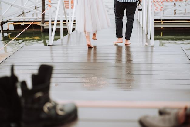 埠頭を背景に結婚したばかりの足元新郎新婦が埠頭を裸足で歩く。