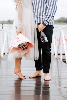 埠頭で結婚したばかりの足。桟橋で裸足で新郎新婦の足。