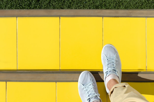Foots in sneakers are on stairs covered with yellow tiles, top view