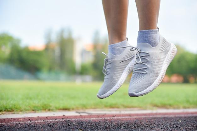Foots женщина в спорт обувает скакать на предпосылку поля зеленой травы.