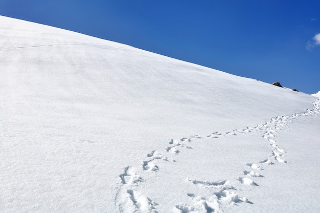 Footsprint on the hill covered with snow