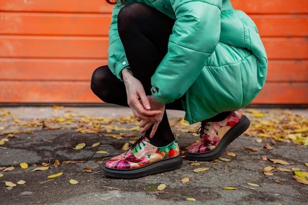 カラフルなプリントの靴を履いて通りのオレンジ色の壁に冬の秋のファッショントレンドフグコートでポーズをとるスタイリッシュな女性の靴のクローズアップ