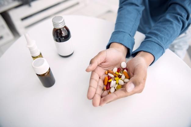 1日。錠剤を保持しているアフリカ系アメリカ人の男の子の手のクローズアップ