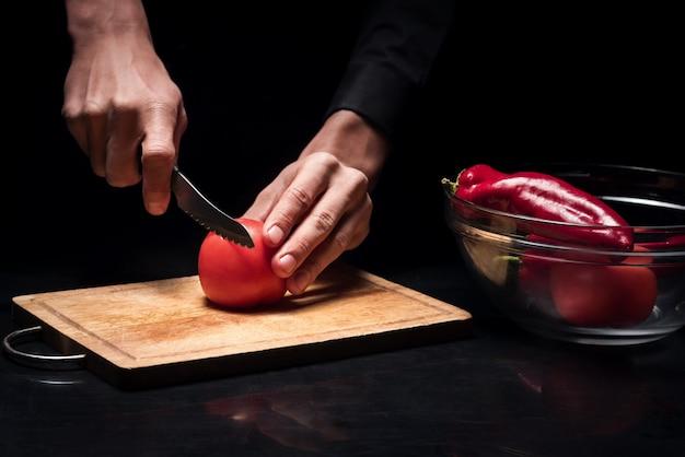 요리를 위해. 닫기 젊은 요리사 망 손 요리 하 고 레스토랑에서 샐러드 야채를 준비하는 동안 토마토를 자르고.