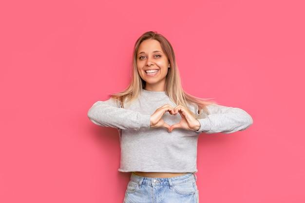 광고에 대한 젊은 백인 꽤 매력적인 금발의 여자는 밝은 색상의 분홍색 벽에 고립 된 그녀의 손으로 심장 모양을 형성 텍스트 또는 디자인을위한 공간을 복사 자선 개념