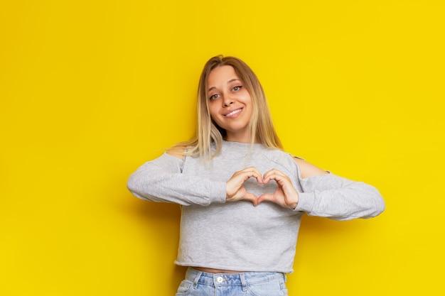 광고에 대한 젊은 백인 꽤 매력적인 금발의 여자는 밝은 색 노란색 벽에 고립 된 그녀의 손으로 심장 모양을 형성 아름다운 귀여운 소녀는 그녀의 사랑 자선을 보여줍니다