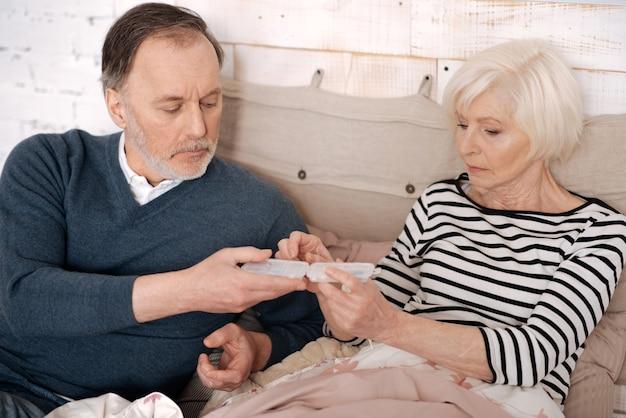 К лучшему. пожилой мужчина дает коробку с таблетками своей пожилой больной жене, лежащей на кровати, укрытой теплым одеялом.