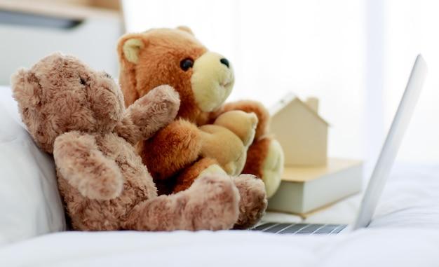가정 침실에서 편안하고 평화로운 장식을 만들기 위해 친구가 노트북을 보며 즐길 수 있도록 두 개의 갈색 사랑스러운 푹신한 테디 베어 장난감이 침대에 창의적으로 놓여 있습니다.
