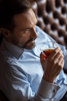 男性のみ。ガラスを保持し、ソファに座ってウイスキーを飲むハンサムな自信を持ってスタイリッシュな男